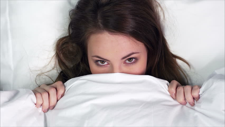 Close-up of a young beauty with a seductive look hiding under the sheets