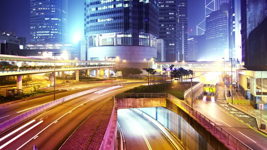 Hong Kong City Night Timelapse. 4K Zoom Out Shot. Office buildings under fast moving cloud. Busy traffic on highway.
