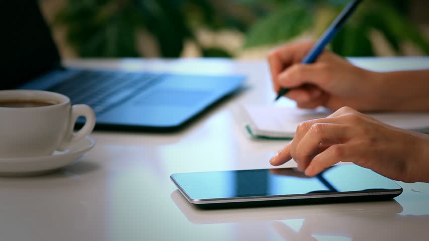 Woman hands with tablet PC and notepad