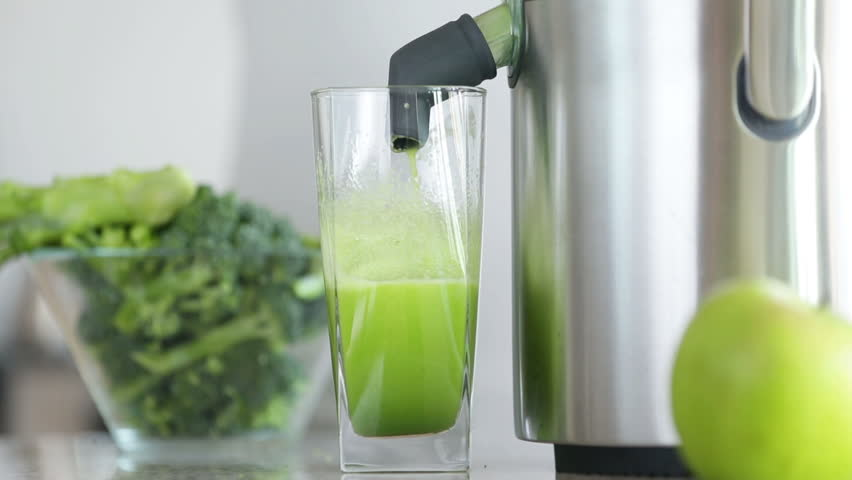 Juicer making green broccoli vegetable juice. Close up of Juicing machine and green juice glass getting full and hand removing glass.