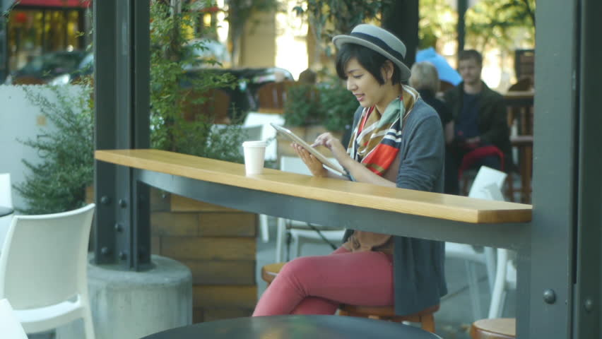 Woman Using Her Digital Tablet At An Urban Cafe (with background activity)