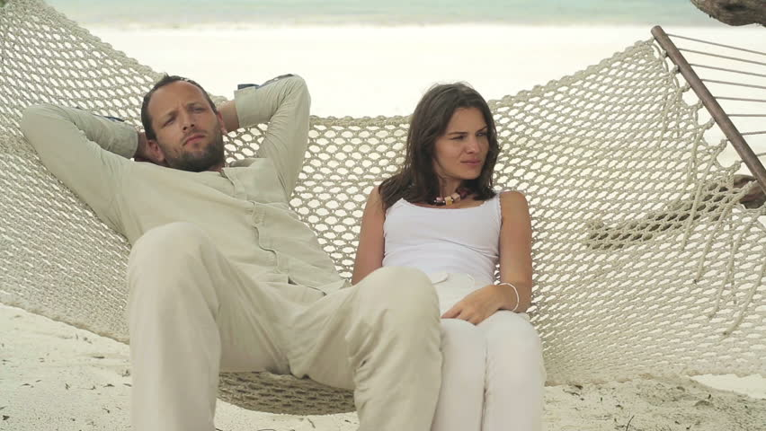 Unhappy, offended couple lying on hammock on the beach