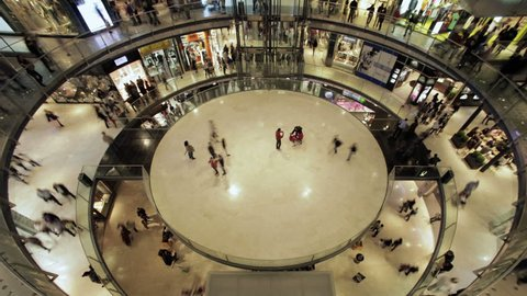 Time lapse of a circular hall in a mall center, with  people walking for shopping. Wide view. 4K