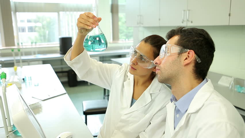 Science students looking at blue chemical together using computer at the university | Shutterstock HD Video #5669075