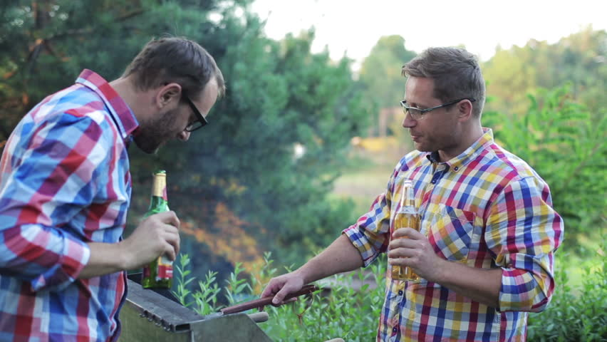 men preparing grill and drinking beer
