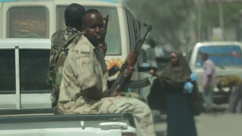 Mogadishu, Somalia, Circa 2013: Following a truck filled with Somali soldiers, women wearing the traditional hijab and other pedestrians are seen along the streets of Mogadishu, Somalia, Circa 2013.