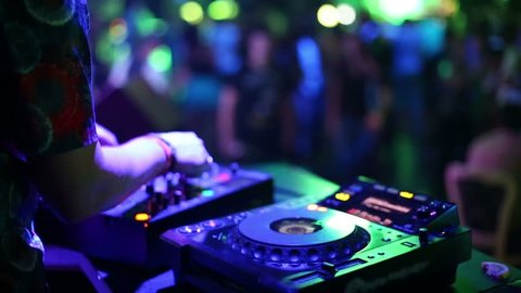 Hands of DJ which mixes music tracks with CD-players and mixer in nightclub