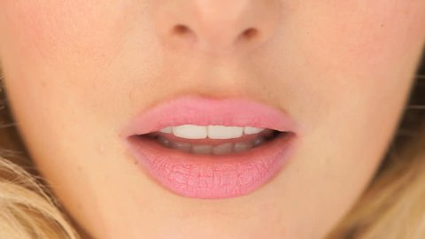 Woman asking for a kiss pursing her lips in a sexy seductive gesture, close up view of her mouth