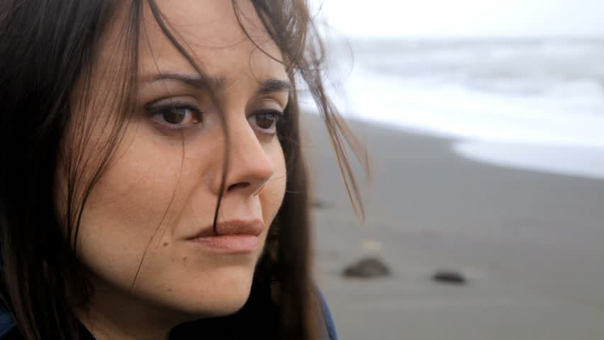 Sad woman crying during storm on the beach closeup