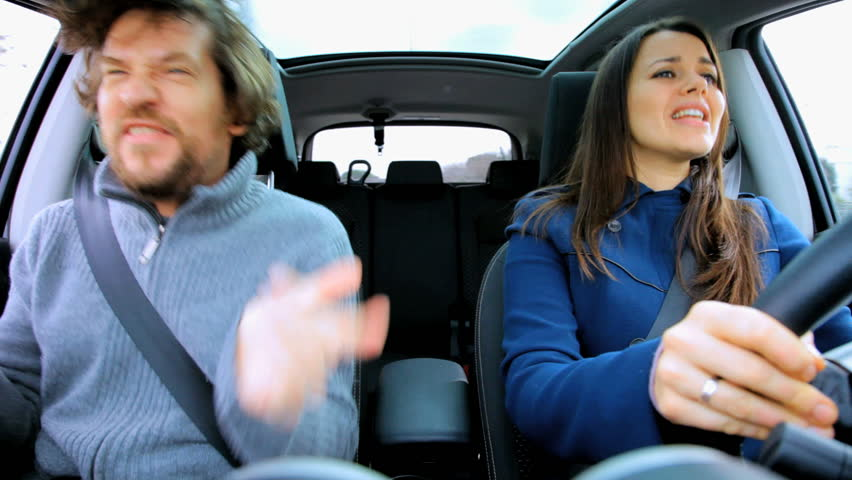 Couple in moving car dancing like crazy happy about going in vacation