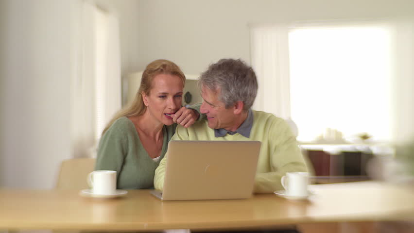 Mature couple using laptop and drinking coffee   Shutterstock HD Video #5684552