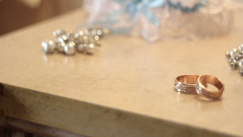 bridal bouquet and gold rings on the table