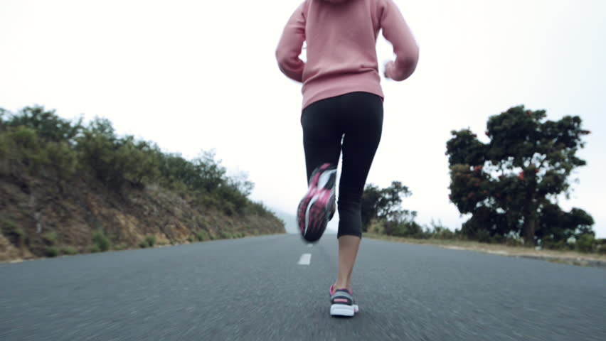 woman running on road close up shoes steadicam shot