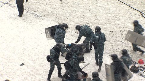 KIEV, UKRAINE - JANUARY 21, 2014: Police beating and arresting protesters doctors during clashes on the street Grushevskogo.