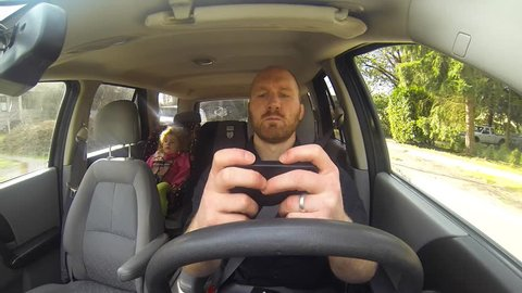 This bad parent is texting and driving with his daughter in the car