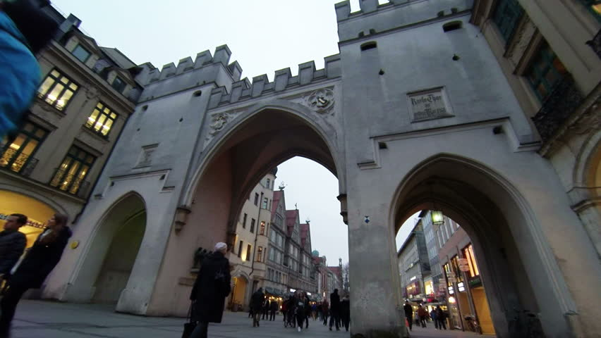 MUNICH, GERMANY – FEBRUARY 05, 2014: Pedestrian slow motion against The Karlstor at Stachus in Munich is one of four main gates of the medieval city wall, winter at evening view.