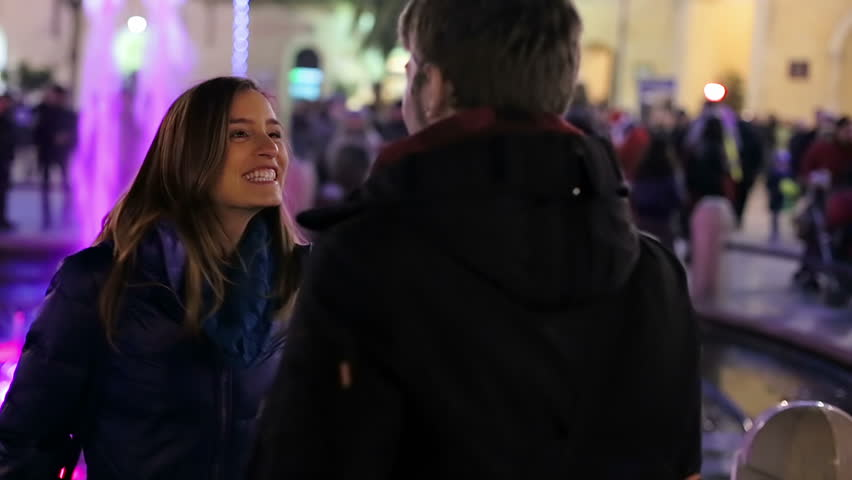 beautiful smiling couple meeting in front of a fountain at night