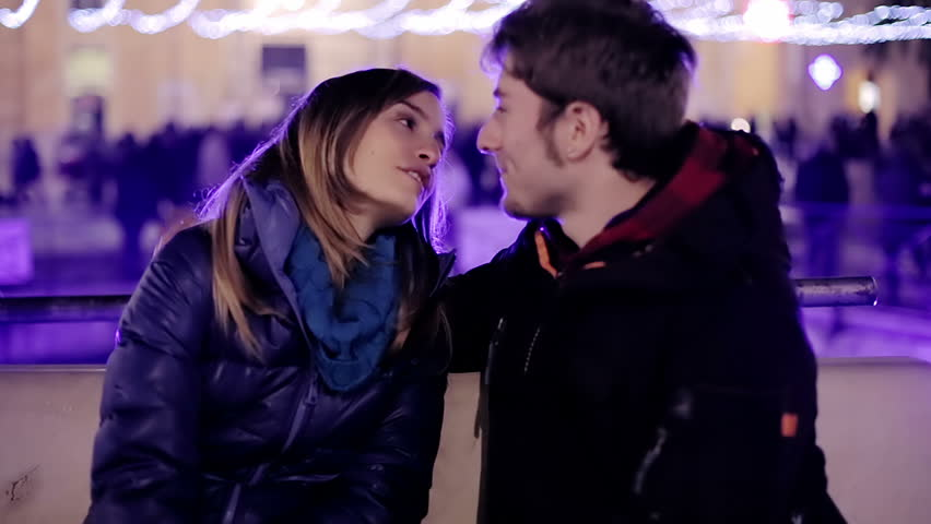 Young couple hugging with fountain on background in the night