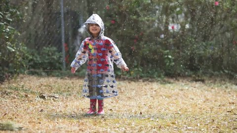 little girl jumping and spinning in the rain, with raincoat and boots