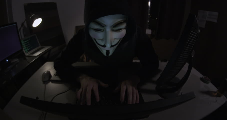 NEW YORK, NY, USA - CIRCA 2013: A hacker activist sits at their laptop computer in a grungy apartment. They are wearing a Guy Fawkes mask which has become an iconic symbol of online social movements
