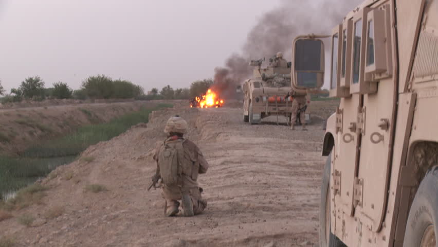 Marine crouches down near his Humvee while vehicle in road is in flames