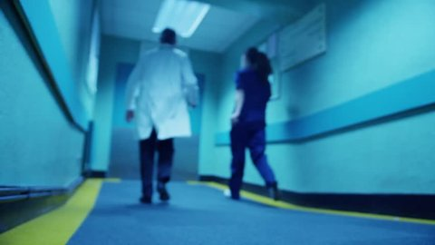 Hospital emergency team rush a patient on a gurney to the operating theater, as seen from the patient's point of view.