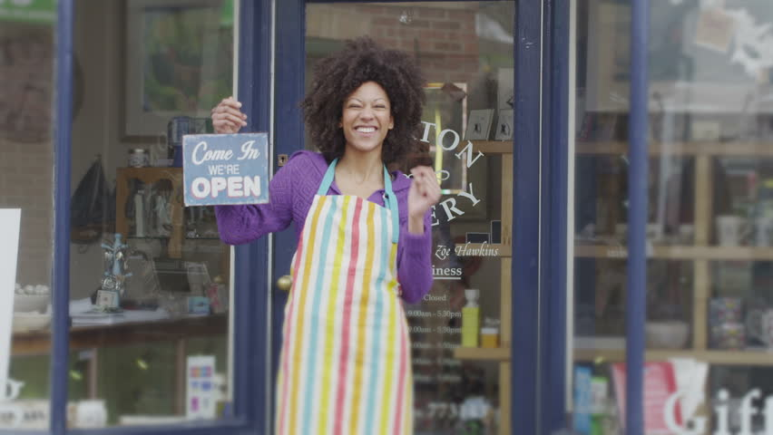 Happy female shopkeeper holds up a sign to show she is open for business | Shutterstock HD Video #5784674