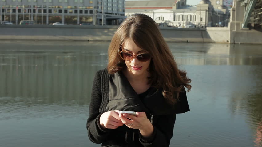 Pretty girl sending text message from her phone against city | Shutterstock HD Video #5788700