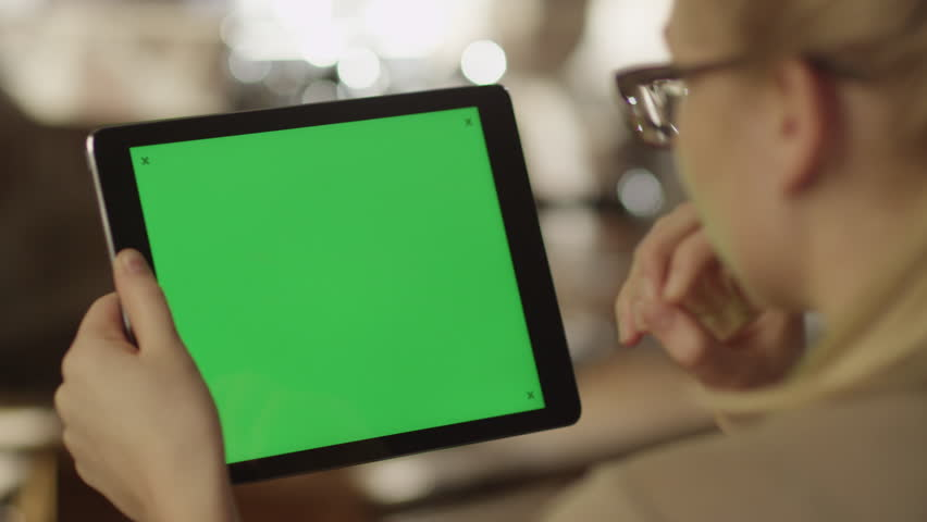 Girl Using Tablet PC with Green Screen. Shot on RED Digital Cinema Camera in 4K (ultra-high definition (UHD)), so you can easily crop, rotate and zoom. Easy for tracking and keying. ProRes HQ codec.   | Shutterstock HD Video #5793353