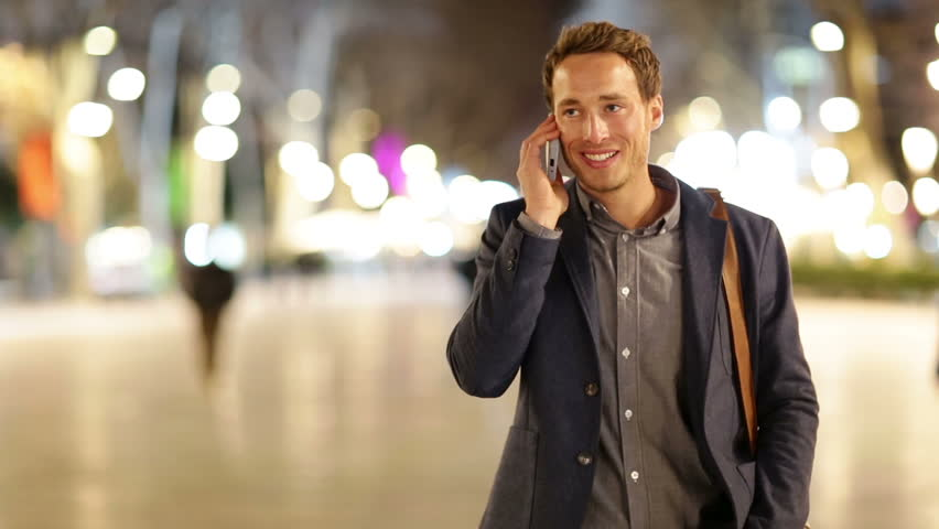 Smart phone man calling on mobile phone at night on La Rambla in Barcelona. Handsome young business man talking on smartphone and walking away smiling happy wearing suit jacket outdoors. | Shutterstock HD Video #5808236