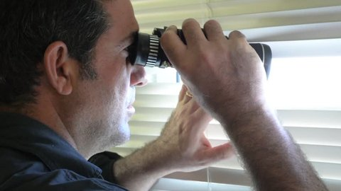 Man (age 35-40 ) looks and searches with binoculars and  looks out through Venetian blinds. Concept footage of curious, spy, nosy man.