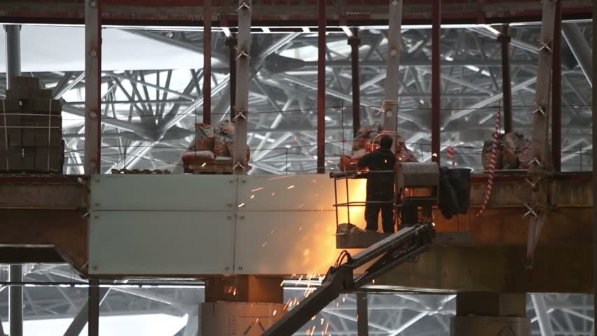 Worker cuts metal on construction of new modern building