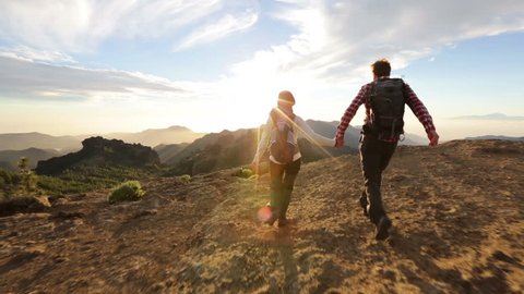 Happy couple cheering and running in nature. Hiking man and woman raising arms excited in celebration outdoors. Hikers cheerful at sunset in mountain by Roque Nublo, Gran Canaria, Canary Islands