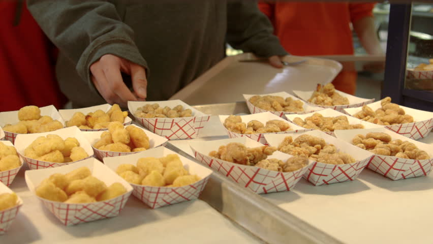 Teenage high school student in cafeteria lunch line selects fried food.