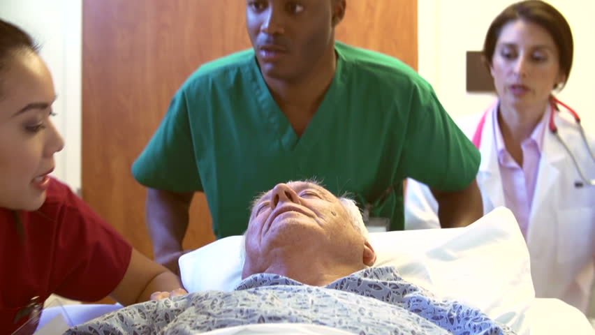 Camera follows senior male patient as he is wheeled along hospital coridoor on trolley. | Shutterstock HD Video #5856194