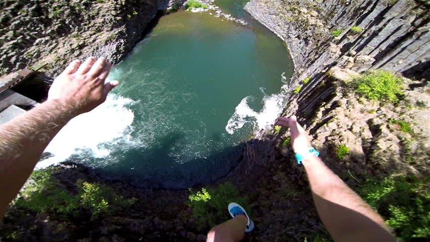 Extremely High POV Cliff Jump into Water above a Waterfall Trees and Rocks Below on a Beautiful Sunny Day in Summer in the Forest with a Thumbs Up to Bystanders Extreme Fun Point of View Head Camera | Shutterstock Video #5882156