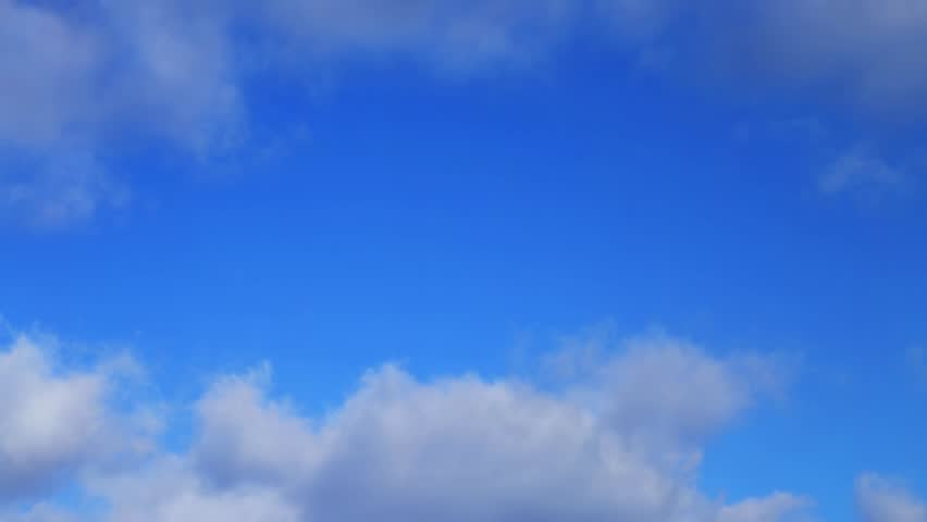 One minute long loop features white clouds floating through a deep blue sky. Fade transition at end allows for looping.