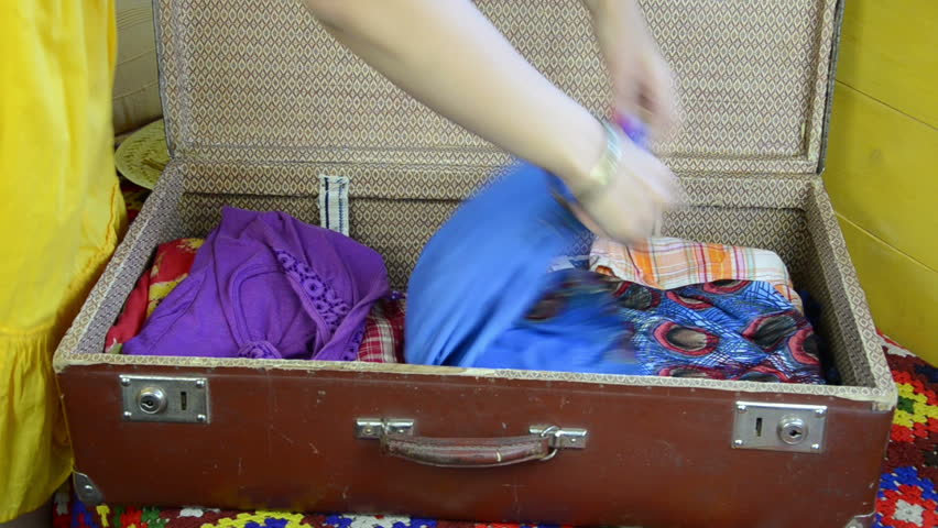 woman hands with red polished nails folds blue long dress and closes the suitcase