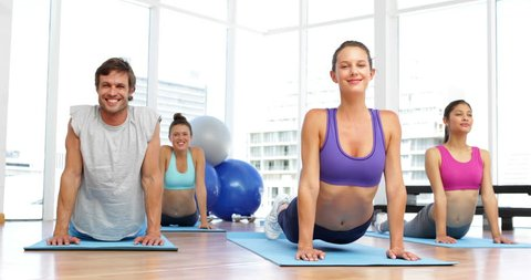 Yoga class doing cobra pose together on exercise mats at the gym