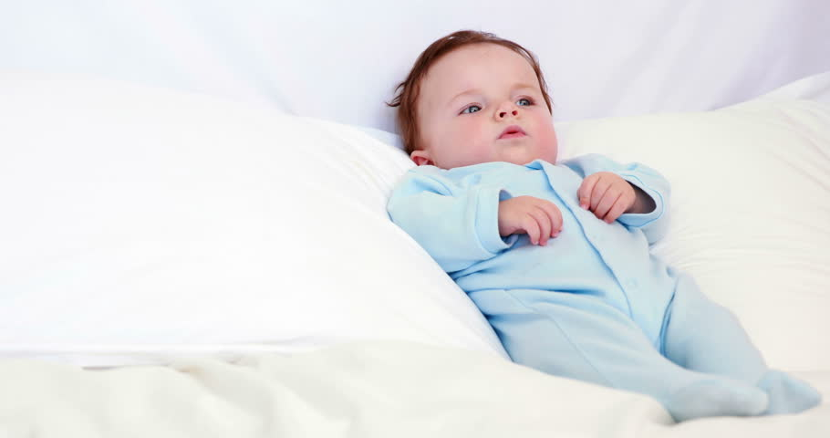 Baby boy in blue babygro lying on pillows at home in bedroom
