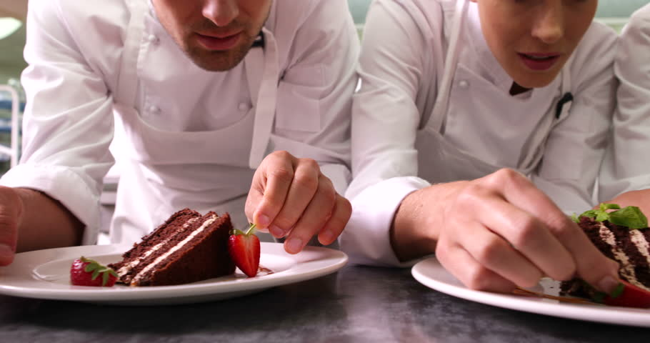 Line of chefs garnishing dessert plates with mint leaves and strawberries in a commercial kitchen