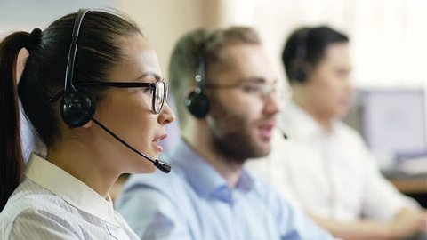 Hot-line operators with headphones consulting clients