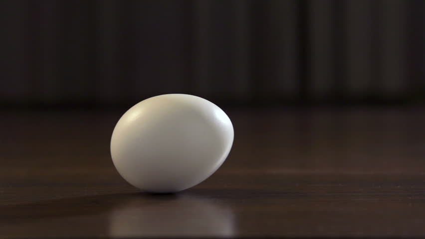 An egg is rolling across the table. Slow motion. Filmed at 250 fps