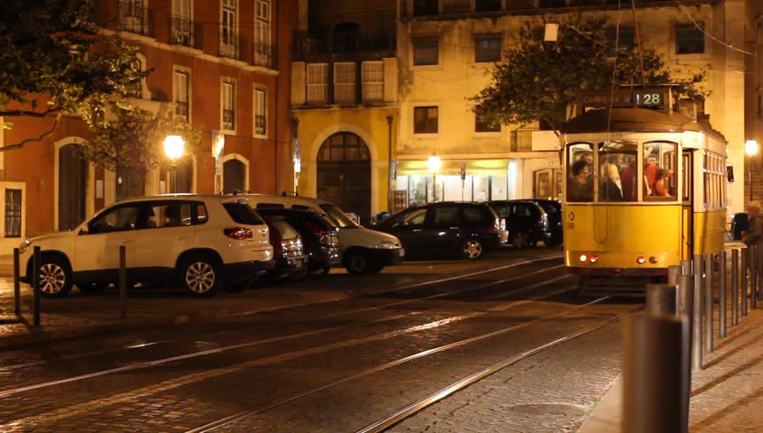 LISBON, PORTUGAL - OCTOBER 26 : Lisbon night scene - two vintage yellow trams arriving simultaneously at the tram station letting passengers out on October 26th 2013 in Lisbon, Portugal