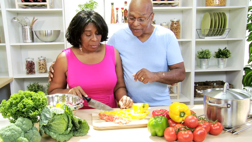 Retired African American couple domestic kitchen preparing fresh tasty organic vegetables as part modern healthy lifestyle diet - Retired Couple Preparing Healthy Organic Vegetables