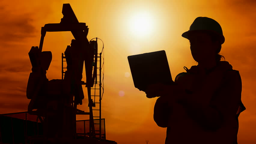 Silhouette worker and oil pump ; Silhouette worker-engineers which controls the oil pump with a laptop ,against the sunset,video clip