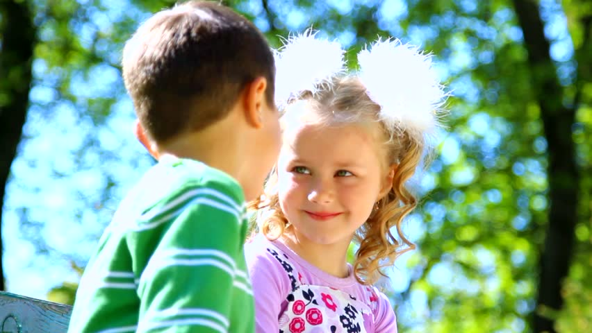 Little boy is kissing pretty girl closeup portrait cute couple sequence beautiful kids on bench cute couple in love boy kissing pretty girl altavistaventures Images