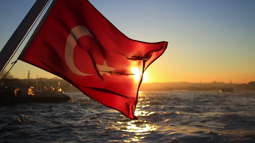Turkish flag waving on the stern of an Istanbul Ship at sunset
