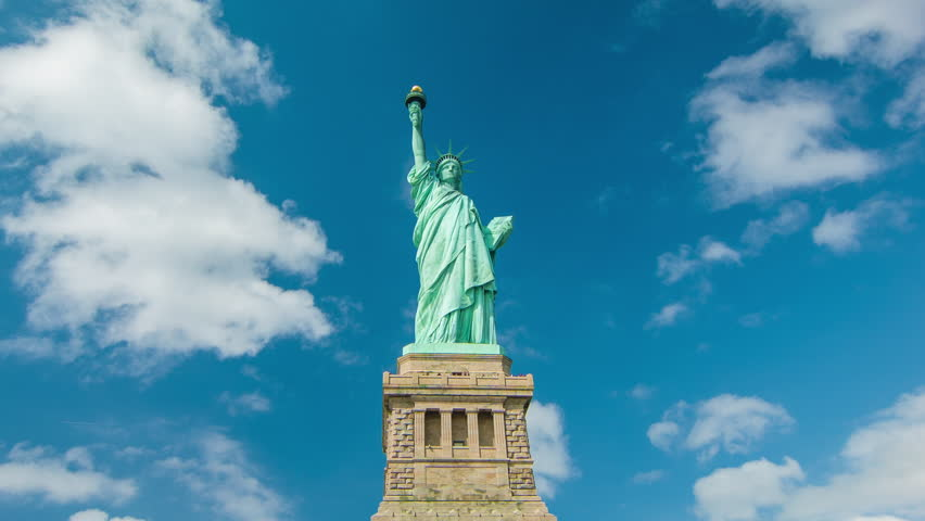 The Statue of Liberty (Wide Shot) with Moving White Clouds in a Blue Sky Background. | Shutterstock HD Video #6074354