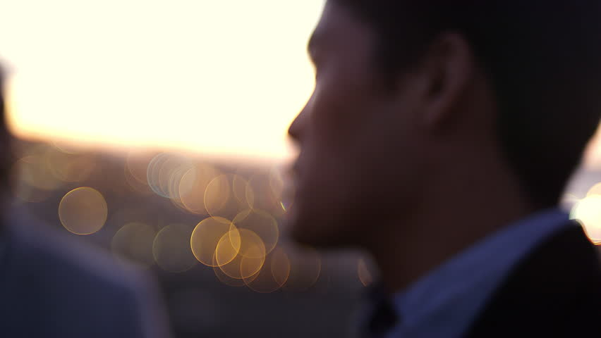 Close up of a man laughing with friends at dusk with some sweet bokeh behind him